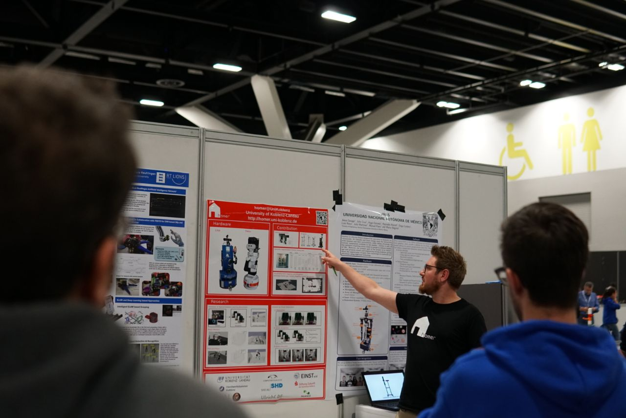Raphael presented the poster. Here he is pointing at Scratchy, a low cost autonomous robot we developed for research and robot competitions