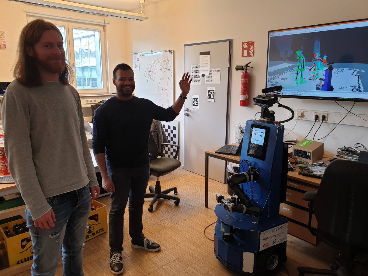 Manuel and Farabi at work testing gesture recognition on Lisa (see the screen on the right for a visualization of the detected poses). This picture was taken last week before the cancellation of all on-campus courses, so excuse the lack of social distancing ;-)